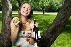 Muchacha de risa con una pera y un vino Foto de archivo libre de regalías
