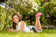 Muchacha de risa del estudiante con la hierba de mentira de los auriculares Fotos de archivo libres de regalías