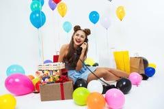 Muchacha de risa después de la gran celebración del cumpleaños que habla en el teléfono Imagen de archivo