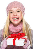 Muchacha de risa en el sombrero y la bufanda del invierno que celebran la presentación de la caja Foto de archivo