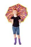 Muchacha de risa en los cargadores del programa inicial de goma bajo el paraguas Foto de archivo libre de regalías