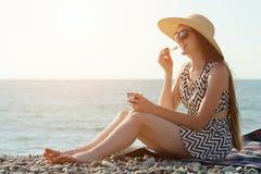Muchacha de risa en sombrero que come el helado en la playa Día asoleado Imagen de archivo libre de regalías