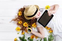Muchacha de risa en un sombrero de paja que descansa sobre la tableta en sus manos imagenes de archivo