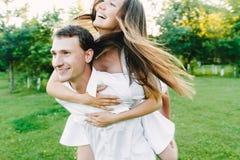 Muchacha de risa feliz que se sienta en su ` s del hombre imagen de archivo