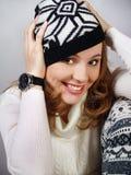Muchacha de risa hermosa en un casquillo hecho punto fotografía de archivo libre de regalías