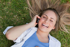 Muchacha de risa joven que miente en ella detrás mientras que habla en el teléfono Fotos de archivo libres de regalías