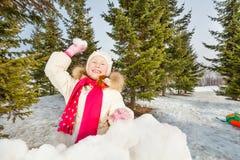 Muchacha de risa lista para lanzar la bola de nieve en bosque Imágenes de archivo libres de regalías