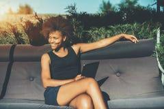 Muchacha de risa negra en el oscilación suave en parque Fotografía de archivo