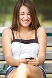 Muchacha de risa que escucha la música en su teléfono Imagen de archivo