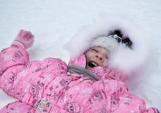 Muchacha de risa que miente en la nieve afuera, invierno Foto de archivo