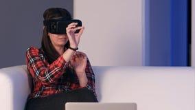 Muchacha de risa que se sienta en el sofá y usar el ordenador portátil vía los vidrios de la realidad virtual Imágenes de archivo libres de regalías