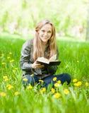Muchacha de risa que se sienta en la hierba con los dientes de león que lee un libro Imágenes de archivo libres de regalías