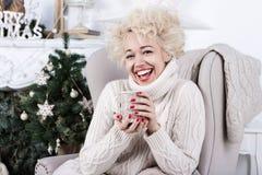 Muchacha de risa que se sienta en la silla Humor de la Navidad foto de archivo