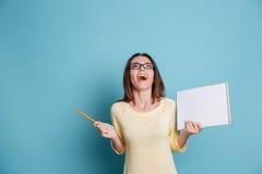 Muchacha de risa que sostiene el cuaderno sobre fondo azul Imagenes de archivo