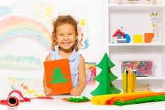 Muchacha de risa que sostiene la tarjeta del cartón con el árbol de Navidad Imagenes de archivo