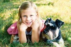Muchacha de risa y su schnauzer miniatura de confianza imagen de archivo libre de regalías