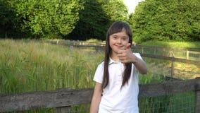 Muchacha de Síndrome de Down que da los pulgares para arriba y que sonríe en el parque almacen de metraje de vídeo
