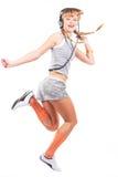 Muchacha de salto en auriculares Fotografía de archivo libre de regalías