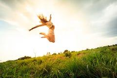 Muchacha de salto en el campo en verano Foto de archivo libre de regalías