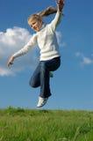 Muchacha de salto en prado Fotografía de archivo