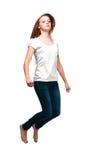 Muchacha de salto en una camiseta blanca Aislado en el fondo blanco Foto de archivo