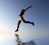 Muchacha de salto fantástica sobre el agua fotografía de archivo