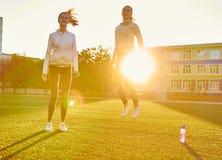 Muchacha de salto sobre el terreno en el contraluz, aptitud por la mañana Deporte, levitación Fotos de archivo libres de regalías