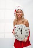 Muchacha de Santa con el reloj de pared Imagen de archivo