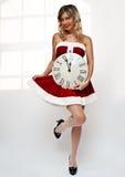 Muchacha de Santa con el reloj de pared Foto de archivo