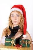 Muchacha de Santa con los presentes que soplan un beso Fotos de archivo