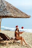 muchacha de santa en la playa con el regalo de la Navidad Imagen de archivo