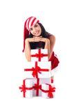 Muchacha de Santa en una pila de regalos. Imagen de archivo