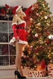 Muchacha de Santa que adorna para la Navidad Imagenes de archivo