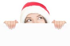 Muchacha de Santa que mira a escondidas sobre tarjeta de la muestra Fotografía de archivo
