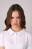 Muchacha de Seious en camiseta Cierre para arriba Fondo blanco Fotos de archivo libres de regalías