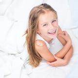 Muchacha de seis años en una cama blanca Imágenes de archivo libres de regalías