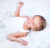 Muchacha de seis años en una cama blanca Fotos de archivo libres de regalías