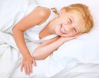 Muchacha de seis años en una cama blanca Imagen de archivo