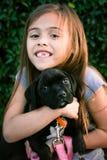 Muchacha de seis años que sostiene el perrito negro del boxeador-pitbull Foto de archivo