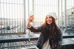 Muchacha de Selfie en la ciudad en la puesta del sol Foto de archivo