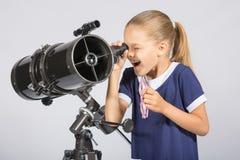 Muchacha de siete años con interés y la mirada abierta de la boca en el telescopio del reflector y miradas en el cielo Foto de archivo libre de regalías
