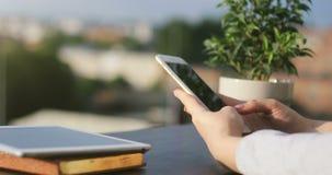 Muchacha de Smartphone que usa el app en serfing que manda un SMS del teléfono Profesional femenino joven hermoso en el teléfono  almacen de video