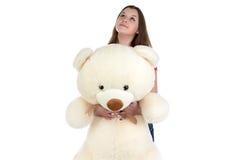 Muchacha de sueño que mira para arriba con el oso de peluche en manos Foto de archivo