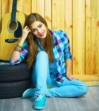 Muchacha de sueño que se sienta en un piso con la guitarra Fotografía de archivo