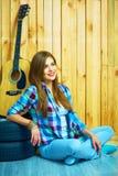 Muchacha de sueño que se sienta en un piso con la guitarra Imagen de archivo