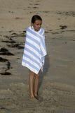 Muchacha de Tan Caucasian envuelta en una toalla rayada que se coloca en el  Imágenes de archivo libres de regalías