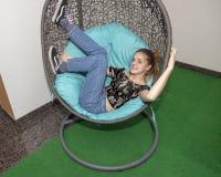 Muchacha de trece años de la cadera que se relaja en una silla del huevo Imagen de archivo libre de regalías