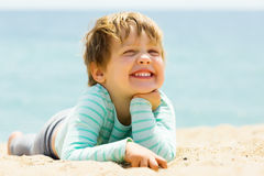 Muchacha de tres años de risa que pone en la playa Imágenes de archivo libres de regalías