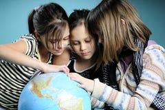 Muchacha de tres blancos que estudia el globo por vacaciones Foto de archivo libre de regalías