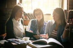 Muchacha de tres estudiantes que aprende junto y que usa p elegante fotografía de archivo